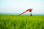 stock photo of rune  - Young lady runing with tissue in green field - JPG