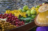 stock photo of floating  - Small boat laden with colourful fruits and vegetables on Damnoen Saduak Floating Market, Thailand ** Note: Visible grain at 100%, best at smaller sizes - JPG