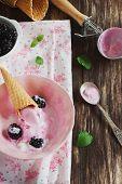 foto of blackberries  - ice cream in a bowl ripe blackberries and mint leaves on the table - JPG