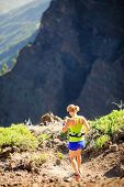 picture of canary  - Young woman running or power walking in mountains on sunny summer day - JPG