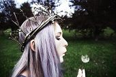 stock photo of hair blowing  - Young woman with purple hair wearing twig crown and blowing on a dandelion - JPG