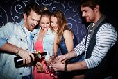 picture of flute  - Happy guy pouring champagne in flutes of friends at party - JPG
