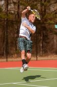 picture of leaping  - A male high school tennis player follows through on leaping overhead shot - JPG