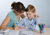 stock photo of homework  - mother helping his son to do homework - JPG