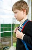 pic of schoolboys  - Schoolboy with a briefcase on the back of a sad looking out the window - JPG