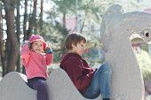 stock photo of crusher  - Sibling children are playing and sitting on concrete park sculpture of animal - JPG