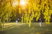stock photo of foreground  - Senior golf player couple putting on green at sunset - JPG