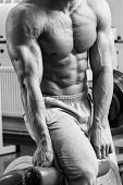 image of abdominal muscle  - A man pumping abdominal muscles in the gym - JPG