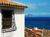 stock photo of grating  - Spanish grated window of old house and sea in background - JPG