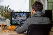 Постер, плакат: Male Gamer Playing Shooting Game On Computer With Snacks Lying On Table