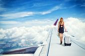 traveler woman walking on an airplane wing  carrying a suitcase Travel concept poster
