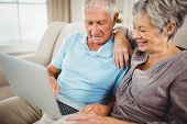 Senior couple sitting on sofa and looking at laptop in living room poster