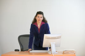 picture of stand up  - Businesswoman standing behind desk with computer - JPG