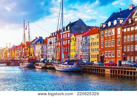 poster of Scenic summer sunset view of Nyhavn pier with color buildings, ships, yachts and other boats in the Old Town of Copenhagen, Denmark