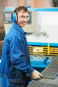 foto of guillotine  - worker at workshop operating guillotine shears machine - JPG