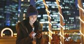 Woman use of smart phone in the city at night, surf online on smart phone with urban city background poster