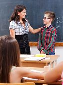 picture of eminent  - Teacher praise eminent math boy at chalkboard in front of the whole class - JPG