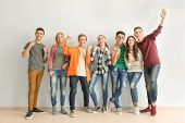 Group of cute teenagers standing near white wall poster