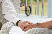 stock photo of holding hands  - seniors holding hands sitting on porch - JPG