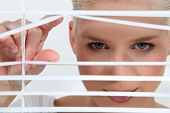 stock photo of voyeur  - a blonde woman looks through blinds - JPG