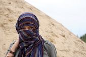 stock photo of yashmak  - Eastern woman in yashmak over the background with sand and sky - JPG