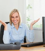 Smiling Woman Sitting Behind Desk Not Having A Clue What To Do Next
