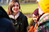 Self-confident young woman surrounded by multi-ethnic friends outdoors in a cold day of winter poster
