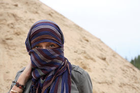 foto of yashmak  - Eastern woman in yashmak over the background with sand and sky - JPG