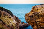 Exotic Cliff Rock, Background Sea   Light Brown Color Rocks And Cliff, Waves Hitting The Rocks poster