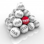 picture of risk  - A pyramid of stacked balls each marked Risk with one reading Reward symbolizing the hidden benefits of taking a risk and overcoming a challenge with a great return on your investment of effort - JPG