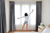 Rear View Of Good Shape And Healthy Asian Young Woman Wake Up In The Morning, She Stretching While O poster
