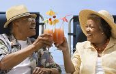 Senior African couple toasting with tropical cocktails