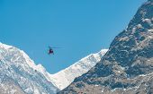 Helicopter Rescue Flying Over The Snow Mountains Of Himalayas Mountains Range, Nepal. poster