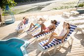 Two Couples Chilling While Sunbathing Near River In The Morning poster