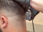 Hairstylist Working With Clipper, Males Nape And Ear, Close Up. Masters Hands In Black Rubber Gloves poster