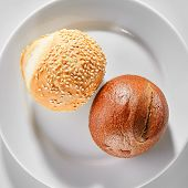Two round buns of rye and wheat flour with sesame seeds top view. Small round brown bread roll and w poster