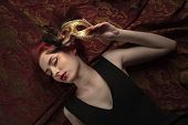 Young Attractive Redheaded Woman In A Black Dress With Golden Carnival Mask. poster