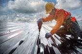 Worker Builder With Hand Drill At Metal Profile Roof Installation Metal Roof Construction poster