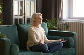 Calm Senior Woman Meditating On Couch At Home poster