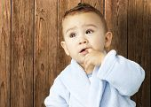pic of housecoat  - portrait of an adorable infant with his finger in his mouth wearing a bathrobe against a wooden background - JPG