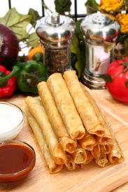 stock photo of flauta  - Stack of chicken taquitos with hot sauce and sour cream in kitchen or restaurant - JPG