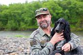Постер, плакат: Среднего в возрасте человек с собакой Русский охотничий спаниель На реке в дождь