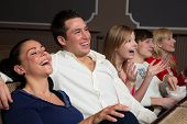 stock photo of laugh out loud  - Laughing people in a cinema or theatre watching a movie or a play - JPG