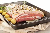 stock photo of pork belly  - Delicious raw pork belly with fresh herbs and potatoes on baking tray - JPG