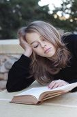 stock photo of sulky  - A sulky teenager lying down reading a book not happy having problems - JPG