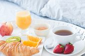 stock photo of pillowcase  - Close-up of tray with tasty breakfast on a bed.