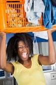 picture of dirty-laundry  - Young African American woman screaming while carrying basket full of dirty clothes at laundry - JPG