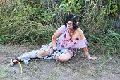 picture of gruesome  - Woman pretending to be a zombie sits on a road - JPG