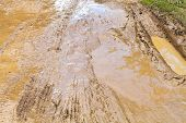 stock photo of mudslide  - mud and puddle at dirt ground road in caucasus mountain - JPG