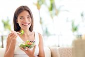 stock photo of sofa  - Healthy lifestyle woman eating salad smiling happy outdoors on beautiful day - JPG